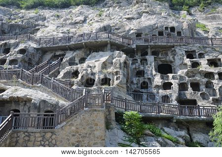 Stairs and walkways on the outside of the ancient Buddha carvings and caves at longmen grottoes in Luoyang China in Henan Province.