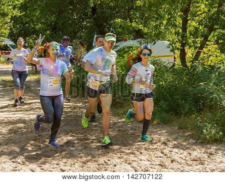 Ukraine, Kyiv - 08/14/2016.  Kyiv color run. Run 5 km from the colors of Holi. Funny and happy runners, stained paint Holi, running towards the finish line.