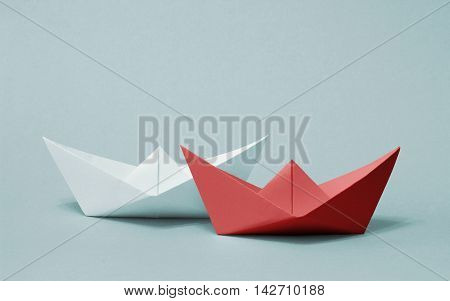 Two paper boats competing with each other. Red and white ships sailing on gray background. Rivalry business success and efficiency concept