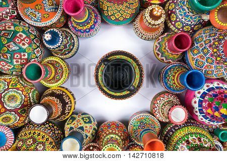 Top view showing a composition of artistic painted handcrafted pottery vases compacted in a circle around a single vase on white background