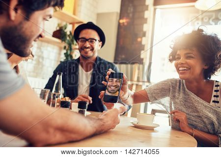 Portrait of happy young friends in cafe and looking at the photos on smart phone. Group of mixed race people sitting around table in a coffee shop and using mobile phone.