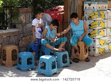 17TH JULY 2016,CALIS,TURKEY:A group of turkish children having a rest while working in a market in Calis in Turkey,17th july 2016