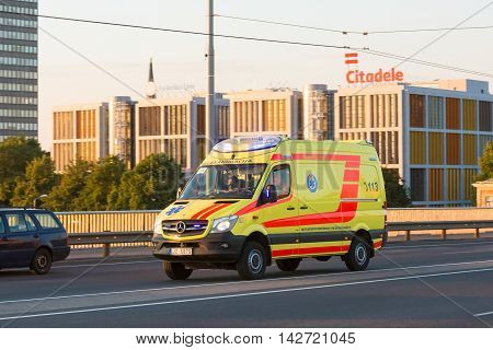 Riga Latvia - June 30 2016: Moving With Siren Bright Yellow Emergency Ambulance Reanimation Van Car On Vansu Bridge. The Building Of Citadele Bank Back From.