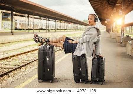 Happy Woman Lies On Suitcases And Listen Music At The Railway Station