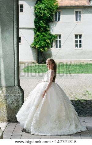 small girl kid with long blonde hair and pretty smiling happy face in prom princess white dress standing sunny day outdoor near building