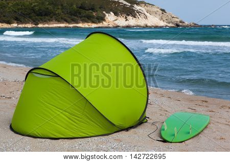 Green tent and surfboard on sea beach