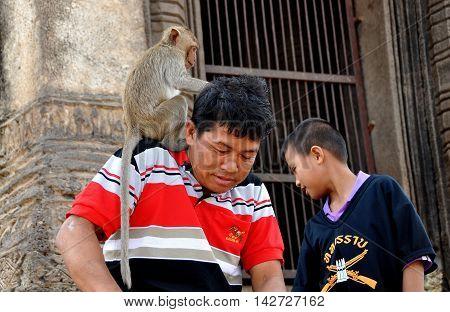 Lopburi Thailand - December 29 2013: Monkey sitting on the shoulder of a Thai man at Wat Phra Prang Sam Yot