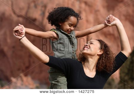 Mother and child playing outdoor holding hands poster