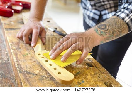 Craftsman using sanding paper on a guitar neck in a workshop for wood. Hard working man with tattoo working with musical instruments.
