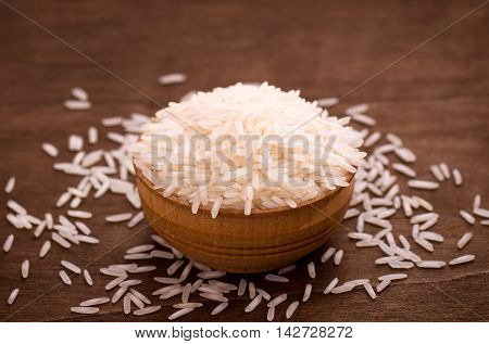 Small wooden bowl of long-grain rice on wooden surface