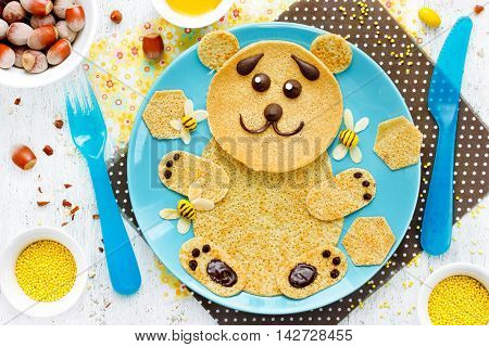 Bear pancakes with honey and nuts for kids breakfast. Animal-shaped pancakes funny food art idea for children top view