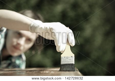 Woman carpenter inspecting her work after treating wood with protection paint. Outdoor protection carpentry hard at work quality control home improvement do-it-yourself concept.