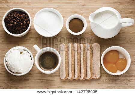 Tiramisu ingredients on wooden background: yolk sugar mascarpone cream savoiardi coffee cocoa top view