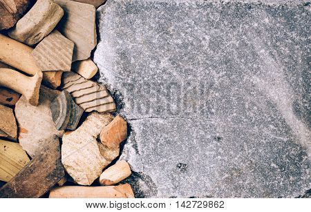 Ceramic shards of antique crockery from left border of marble stone background. Archaeological concept