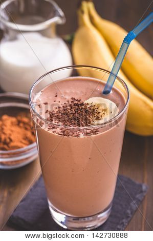 Glass of chocolate banana smoothie with straw