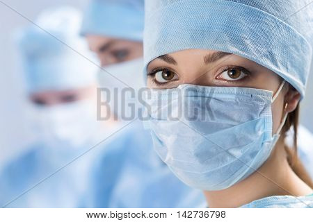 Close up portrait of young female surgeon doctor surrounded by her team. Group of surgeon in operation theatre. Healthcare medical education emergency medical service and surgery concept