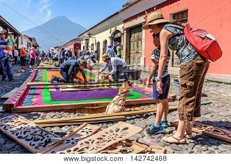 Antigua Guatemala - March 25 2016: Locals make dyed sawdust Good Friday carpets in street with Agua volcano behind for procession in colonial town with most famous Holy Week celebrations in Latin America.