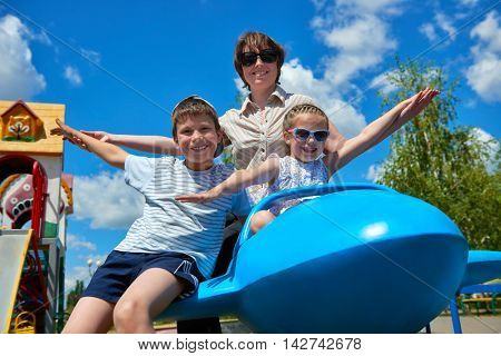 child and woman fly on blue airplane attraction in city park, happy family, summer vacation concept