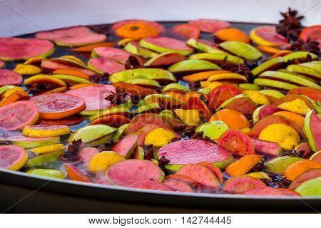 Cooking fruits and spices mulled wine in a large bowl