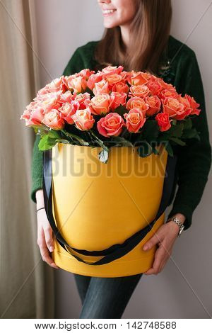 Nice young blonde girl with Blue Eyes and healthy Long Blond Hair smelling flowers holding red roses bouquet in hat box against the plastered wall, wearing jeans and knit sweater.