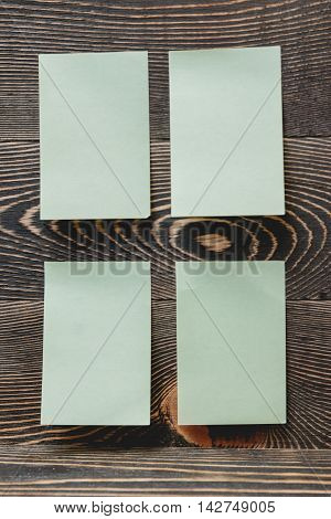 Four Blank Green Stickers on Wooden Wall Background