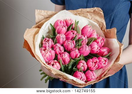 Florist girl with peony flowers or pink tulips Young woman with flower bouquet for birthday or mother's day.