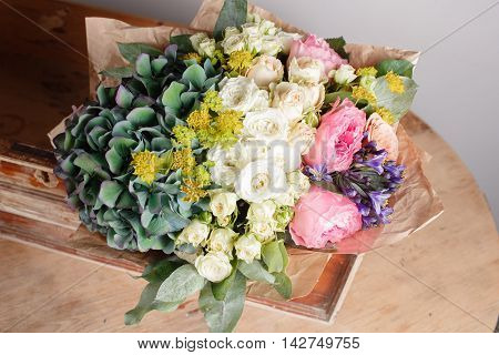 florist did rich bunch flowers light background, wooden box on surface table