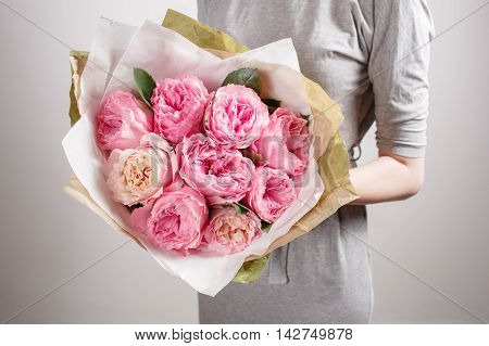 Florist girl with peony flowers or pink garden roses. Young woman with flower bouquet for birthday or mother's day.