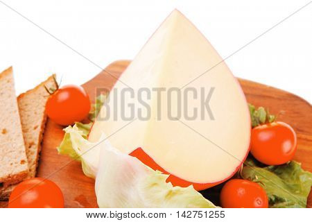 cheese piece on sald with tomato on wood over white