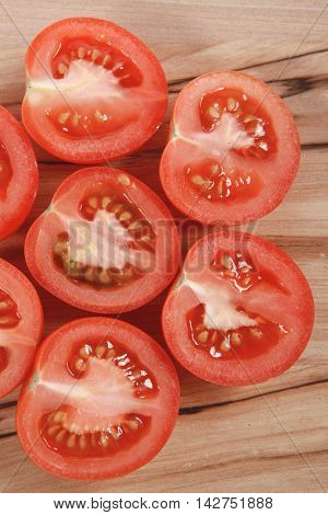 fresh raw tomatoes on light wooden plate isolated over white background
