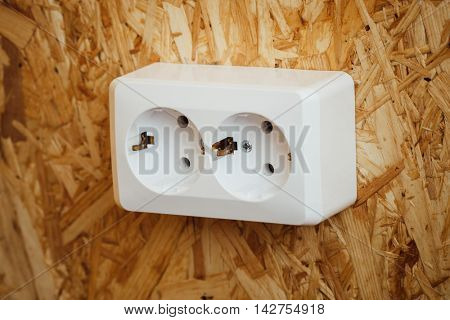 AC power socket, wooden osb wall background