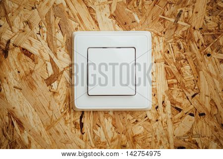 electric light switch, wooden osb background
