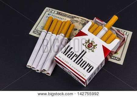 Indianapolis - Circa August 2016: Marlboro Cigarettes and Twenty Dollar Bills Representing the High Costs of Smoking. Marlboro is a product of the Altria Group I