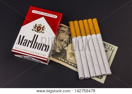 Indianapolis - Circa August 2016: Marlboro Cigarettes and Twenty Dollar Bills Representing the High Costs of Smoking. Marlboro is a product of the Altria Group X