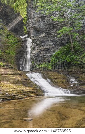 Deckertown Falls a tiered waterfall in Montour Falls New York is topped with early morning beams of sunlight.
