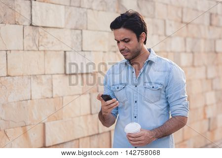 Portrait Of Young Man Drinking Coffee On The Street While Using Mobile Phone