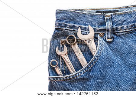 chrome lug wrench and spanner in front blue jeans pocket on white isolated background. Copy space for text
