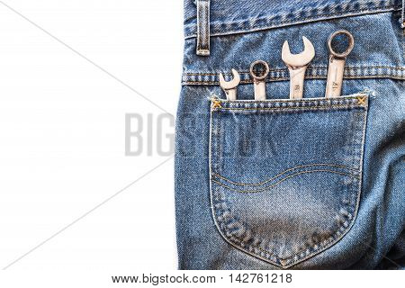 chrome lug wrench and spanner in back blue jeans pocket on white isolated background. Copy space for text poster