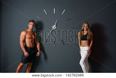 Sport time. Concept. Attractive athletes posing with clock