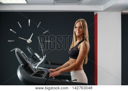 Sport time. Beautiful sporty girl exercising on treadmill