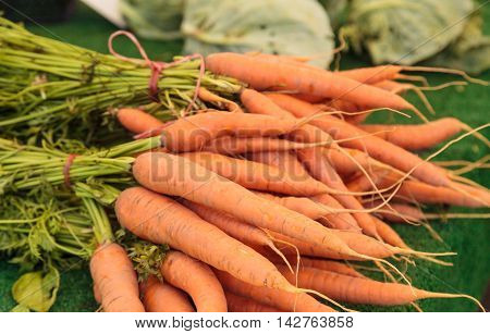 Orange carrots grown and harvested in Southern California and displayed at a farmers market.