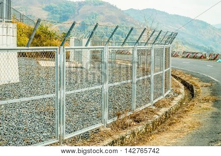 The Chain Link Fence Roadside. Mountain view