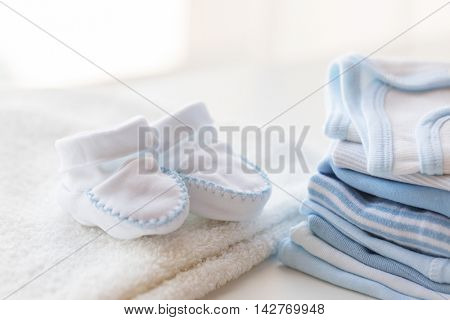 clothing, babyhood, motherhood and object concept - close up of white baby bootees, towel and pile of clothes for newborn boy