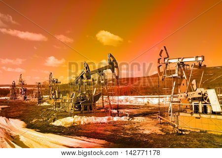 industrial landscape Oil pumps in the field on a background of sky on a sunny day in early spring instagram filter