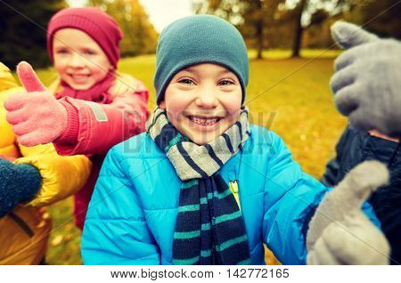 childhood, leisure, friendship and people concept - group of happy kids showing thumbs up in autumn park