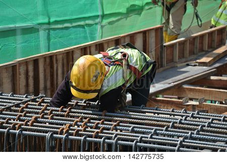 MALACCA, MALAYSIA -JUNE 27, 2016: Construction workers fabricating steel reinforcement bar at the construction site in Malacca, Malaysia. The reinforcement bar was ties together using tiny wire.