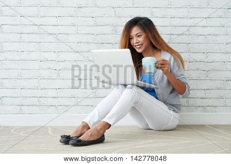 Young Filipino woman with cup of coffee watching tv shows on laptop