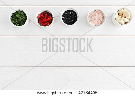 Food seasoning variety on white wooden background, flat lay. Bowls with black and pink sea salt, parsley, chili and garlic, free space. Natural organic flavoring, cooking concept