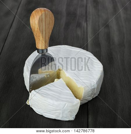 Fresh brie cheese and cheese knife on rustic dark wooden table