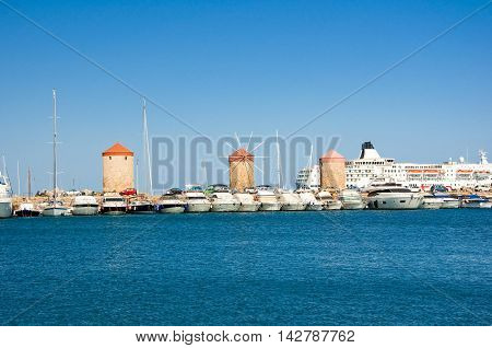 Old windmills in harbour of Rodes Greece.